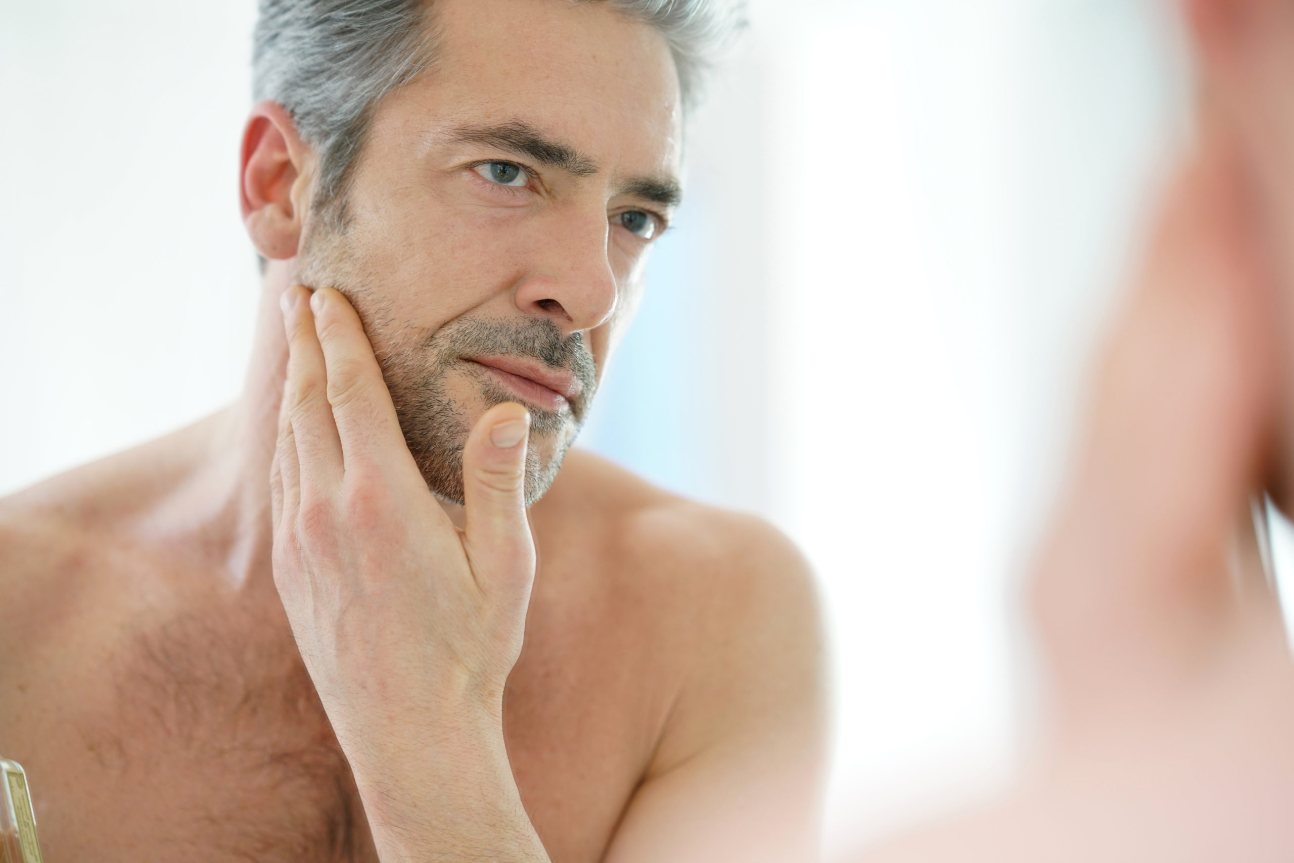portrait-of-mature-man-in-front-of-mirror-applying-facial-cream